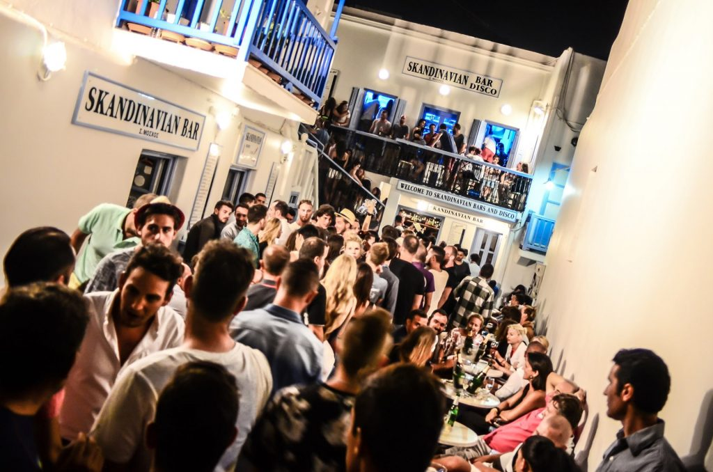Crowds gathering outside the Skandinavian Bar & Disco in Mykonos having fun and partying.
